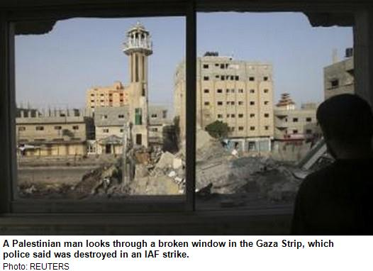 a-palestinian-man-looks-through-a-broken-window-in-the-gaza-strip-which-police-said-was-destroyed-in-an-iaf-strikee