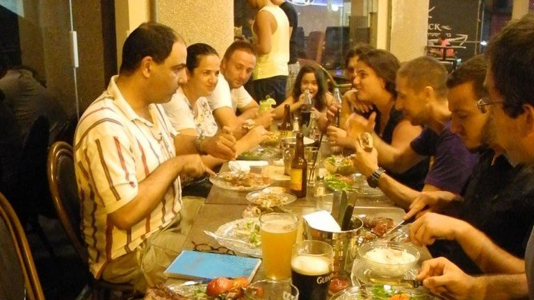 Yigal Rechtman, left, and a full table at Archies bar and restaurant in Ashkelon on Tuesday night. (photo credit: Melanie Lidman/Times of Israel)