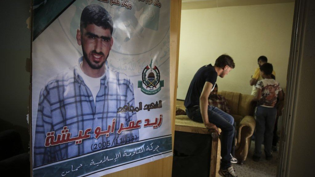 A poster of Amer Abu Aysha hangs on the door inside his family home in Hebron, in the West Bank, which was bombed by IDF overnight, July 1, 2014. (photo credit: Hadas Parush/Flash90)