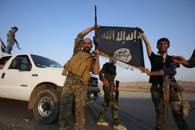 Iraqi Shiite militia fighters hold the Islamic State flag as they celebrate after breaking the siege of Amerli by Islamic State militants